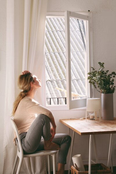 woman-sitting-on-a-chair-next-to-a-window-4112894
