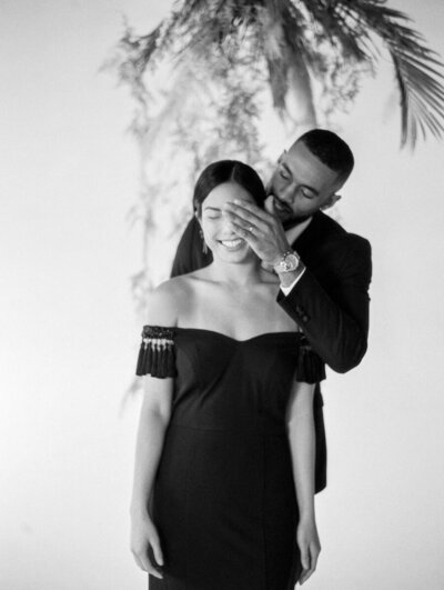 Interracial black and asian couple smile and laugh with bride wearing a black Tadashi Shoji wedding gown and the groom wearing a black Tuxedo and gold watch while standing under gold ferns and spanish moss smiling.