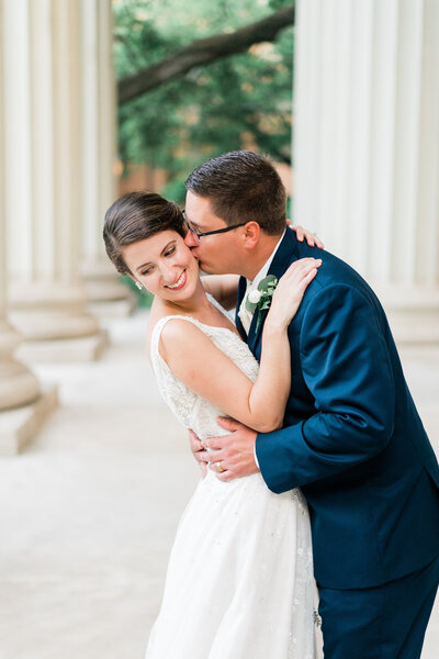 Groom kissing bride in front of columns in Alabama