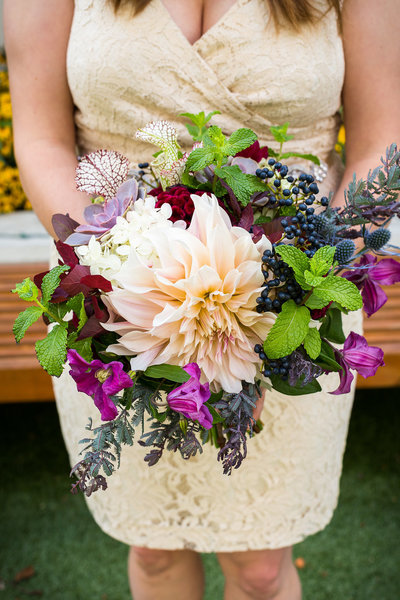 Bride holding summer wedding bouquet with cafe au lait dahlias.