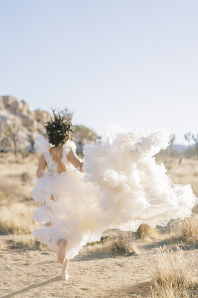 bride running away with a big puffy wedding dress  in Joshua Tree