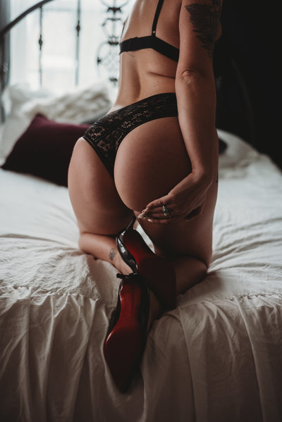 Black underwear on a woman in Christian Louboutin Heels.