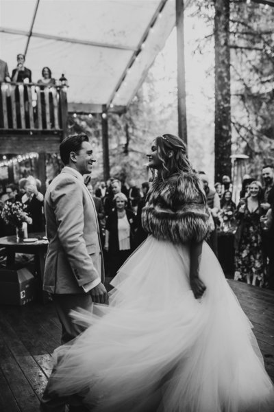 black and white photo of couple during first dance with brides swooshy wedding dress at Raven Glacier Lodge