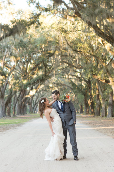 bride and groom kissing in avenue of the oaks at wormsloe historic site in savannah georgia