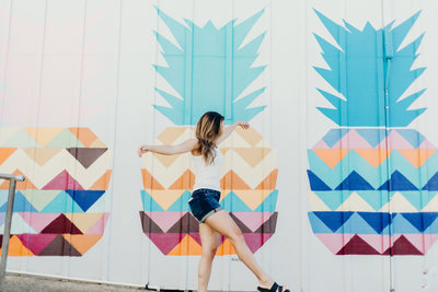 woman standing next to colorful wall