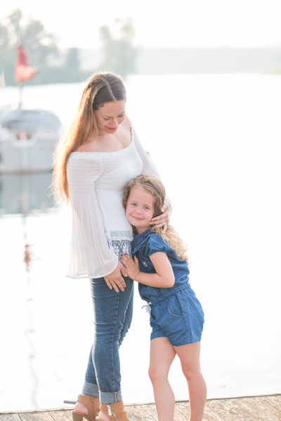 Mother embraces her daughter while standing on a dock