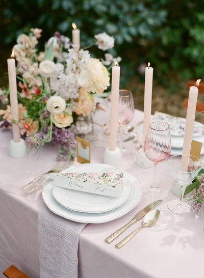Plates and candles arranged on a table with flowers for a wedding