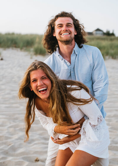 couple smiling and laughing on the beach