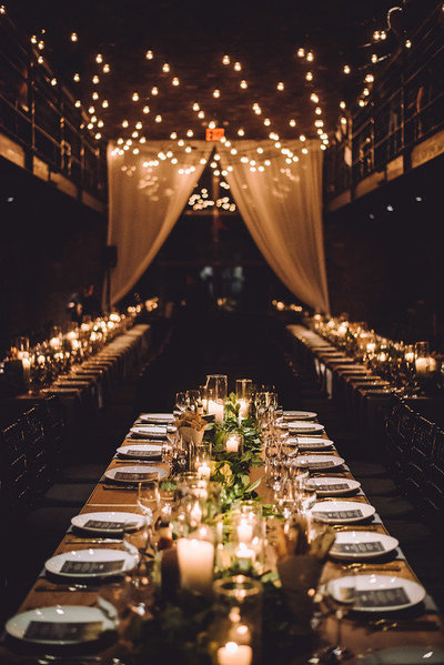 A romantic and moody wedding reception with long banquet tables in an old warehouse in Brooklyn.
