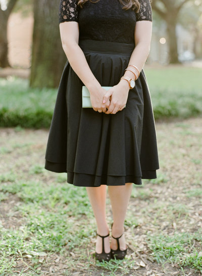 Lyndi standing in the grass in a black dress holding a green clutch wearing cute shoes