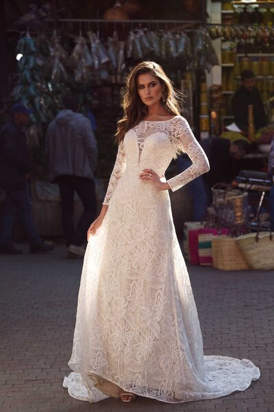 Oh sweet Amira, how you are a love story on your own with your curving conservative neckline and beguiling long sleeves. The unforgettable design elongates the body and falls gracefully from the waist down. The nude undertone of the sweetheart bodice is visible through the same mesmerising lace as seen on Azaria. The sweeping neckline which frames her bride's face plunges low into a soft V-back before pooling into a sheer lace train behind. Amira is kind as she is alluring with her lusting conservative nature. The nude undertone warms complexions as does the sand hue which is also available in Amira.