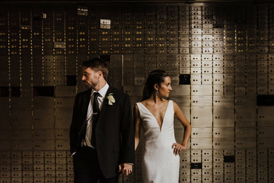 bride & groom standing against wall