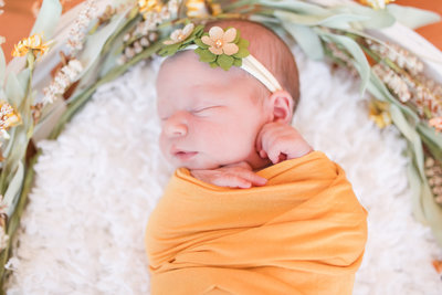 Newborn baby swaddled in yellow swaddle with floral headband sleeps during newborn photography session