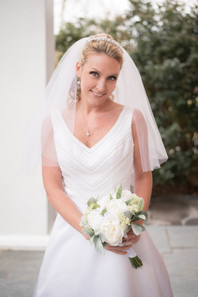 winter bride with white bouquet on the front porch of the Golden Horseshoe Inn wedding venue