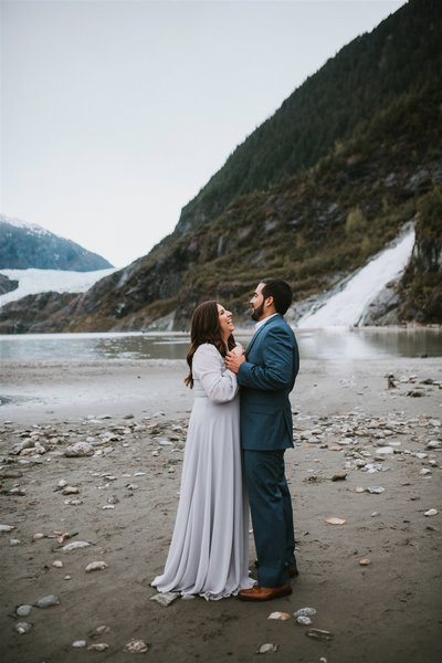 couple holding hands and laughing in a suit and dress with Nugget Falls in Juneau in the background