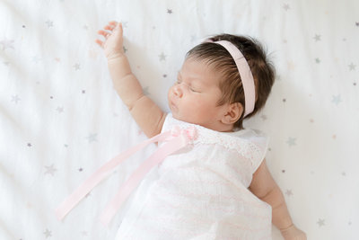 baby-girl-naps-in-crib-white-sheets