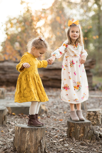 Two sisters standing on wooden tree stumps holding hands