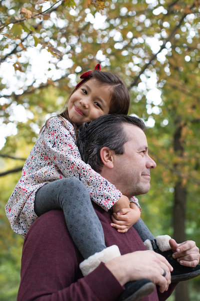 Portrait of little girl on her father's shoulders in Prospect Park