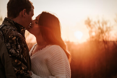 Engaged couple sharing an intimate kiss as the sun sets behind them