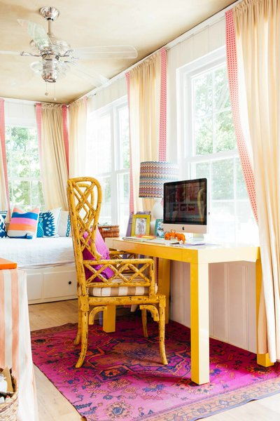 A colorful  interior design studio with day bed and yellow computer desk.