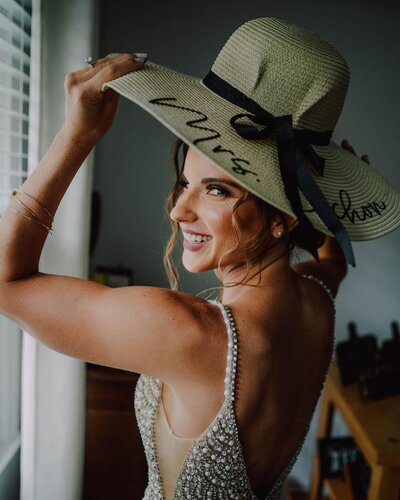 bride mischievously looks at camera while wearing a white gown and holding onto her custom wide brimmed hat before her tiny wedding shot by wedding photographer in philadelphia alex medvick