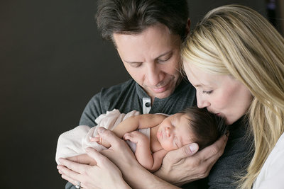 Parents of newborn baby cradling him in Denver portrait studio