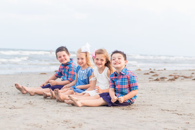 children sitting on the beach in Galveston Texas