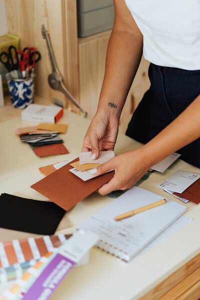 woman sorting paper swatches for custom invitation stationery