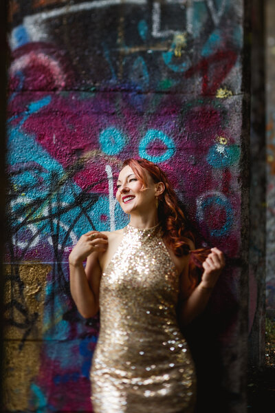 woman in gold dress with graffiti