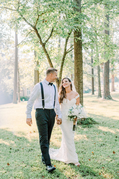 bride and groom laughing and walking together through the trees in Hurricane, Wv