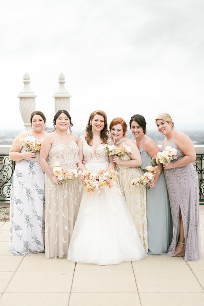 bride stands on the balcony of the brown hotel surrounded by her bridesmaids wearing mismatched dresses in blues, purples, and creams holding their pastel color bouquets by roots floral design