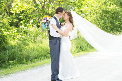 Bride and groom embrace while bride's veil blows on a country road