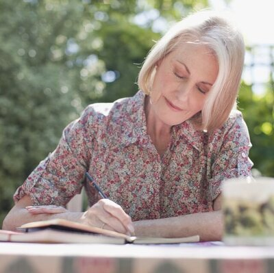 woman-writing-in-journal-at-patio-table-royalty-free-image-1592573678