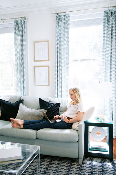 Woman working on her gold laptop while sitting on sofa with pillows