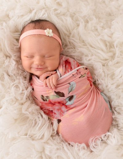 Newborn photography Rochester NY | baby sleeping wearing a grey romper and headband in black/white