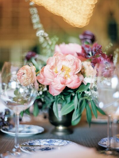 Close up of wedding floral centerpiece with large pink peony surrounded by chic wine glasses, fine china, and bistro lights.