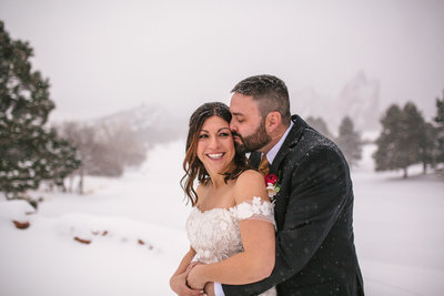 bride and groom cuddling in the snow at winter wedding in Colorado
