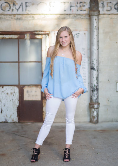 High school senior girl poses for photo in blue shirt and white jeans