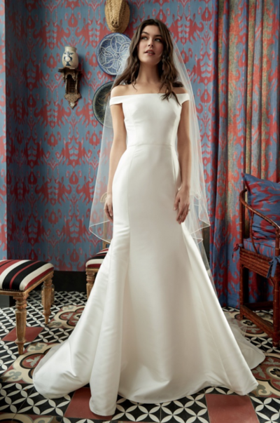 "This Mikado gown boasts a streamlined fit and flare silhouette and is paired with an oh-so-romantic ""kiss the shoulder"" sleeve detailing. With fabric-covered buttons cascading down the back, you cannot help but fall for this modern classic."