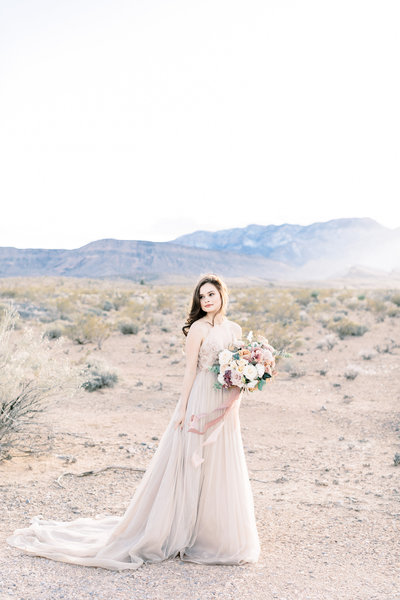 a bride out in the Las Vegas desert in a taupe wedding dress and a lush floral bouquet