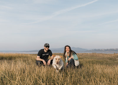 man and woman in field with dog