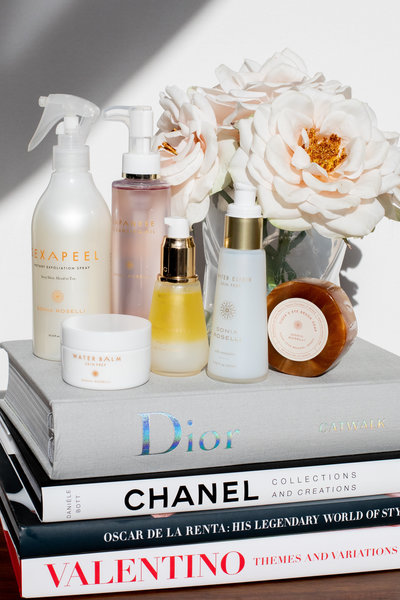 Sonia Roselli Beauty skin prep products stacked atop a stack of books with flowers in a vase