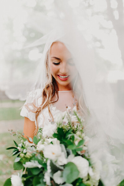 bride looking at flowers under her veil