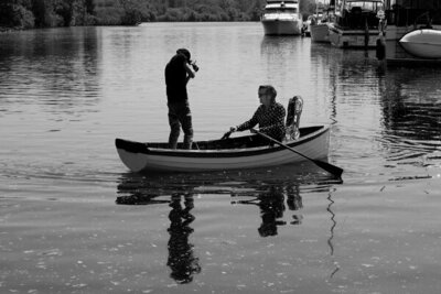 Behind the scenes black and white image Mark Maryanovich standing in row boat while photographing musician Stephen Fearing  who holds oars