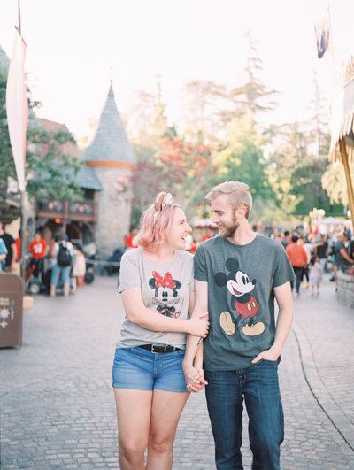 Susannah and her husband walk hand in hand in Disneyland wearing matching Mickey and Minnie Shirts
