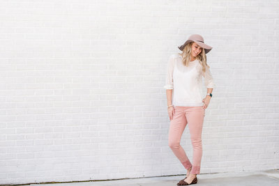 Photographer Amanda Zabrock smiles looking down her shoulder in front of white brick wall wearing a hat, white blouse, and pink pants