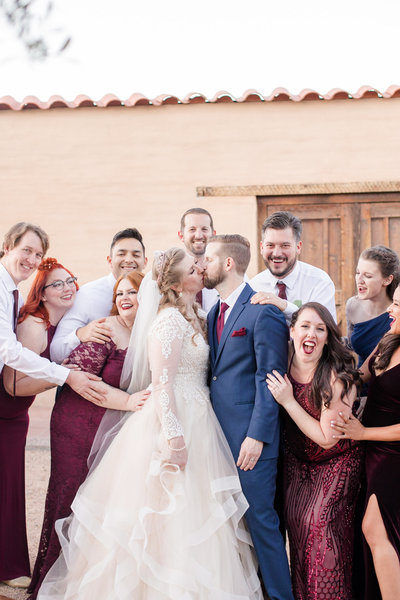 Bridal party celebrating a kissing bride and groom