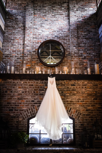 Gown hanging on fireplace, dramatic dress shot, Greengates Farmhouse, Laurel, MS, Mississippi Wedding