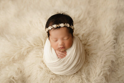 baby girl wrapped in cream on cream flokati