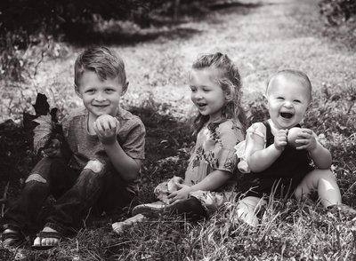 photo of three siblings in orchard.